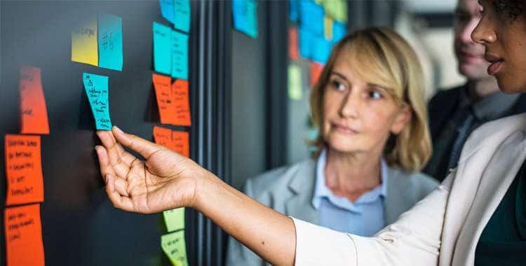 Gerentes de una empresa con tarjetas de colores, organizando tareas de gestión